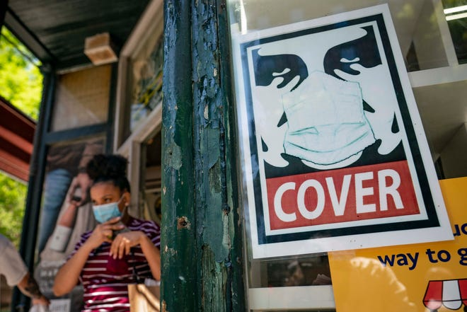 A customer exits a corner market while wearing a protective mask in the SoHo neighborhood of the Manhattan borough of New York in this May 14, 2021, file photo.