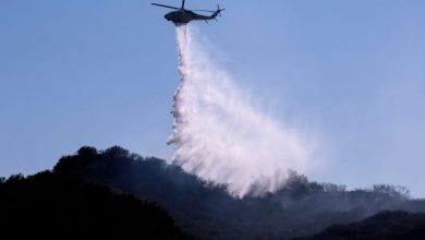 A A helicopter makes a water drop to put out hotspots in a wildfire in Topanga, west of Los Angeles, Monday, July 19, 2021.