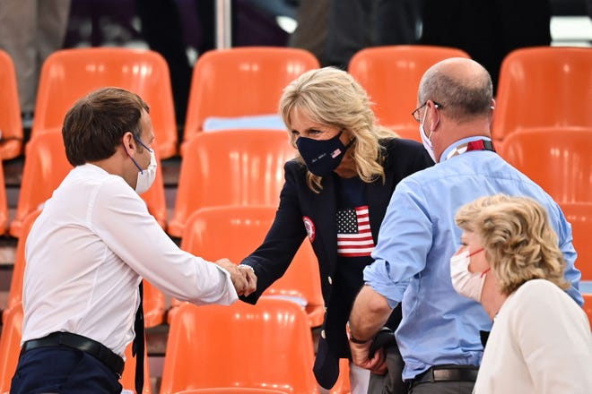 French President Emmanuel Macron and First Lady Jill Biden shake hands prior to attend the women's first round 3x3 basketball game between the USA and France during the Tokyo Olympics on July 24.