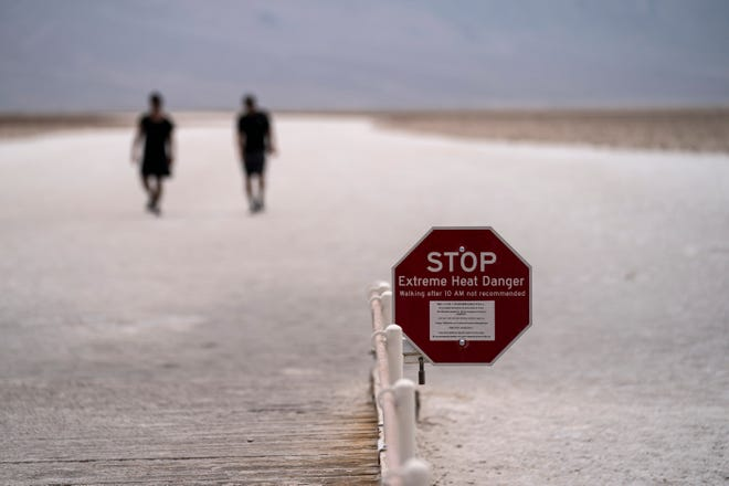 A sign warns of extreme heat danger as people walk on salt flats in Badwater Basin, Sunday, July 11, 2021, in Death Valley National Park, Calif. Death Valley in southeastern California's Mojave Desert reached 128 degrees on Saturday, according to the National Weather Service's reading at Furnace Creek.