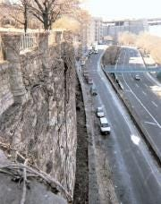 Photo shows the high rock wall supporting the bluff above the Henry Hudson Parkway in New York City before part of the wall collapsed in 2005
