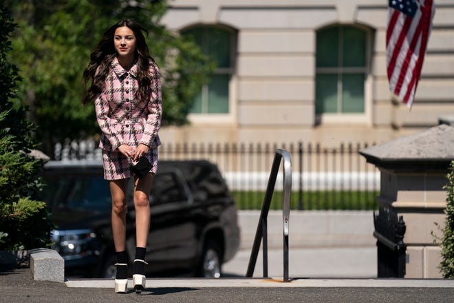 Rodrigo, wearing a pink plaid ensemble with white platform heels, heads to the White House to meet with President Joe Biden and Dr. Anthony Fauci.