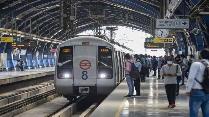 Commuters wait to board a train after resumption of the