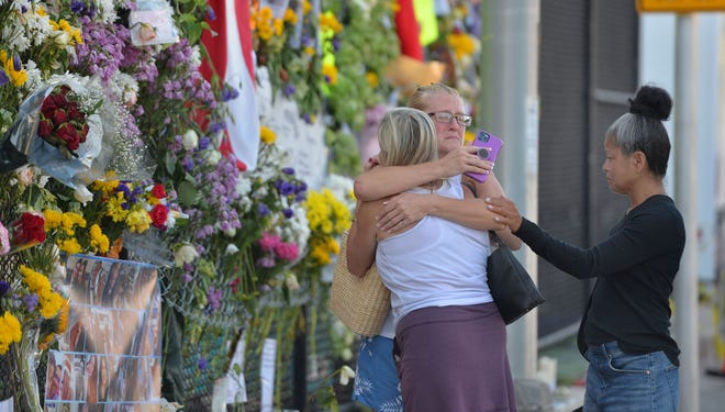 Rain Ruth, center, hugs her sister, Rose, Ruth, left, during their first visit to the memorial wall near Champlain Towers South, with friend Tudcin Reyes, right, on Saturday morning in Surfside, Florida.