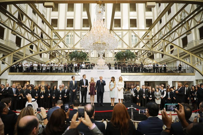 Then presidential nominee Donald Trump and his his family, from left, son Donald Trump Jr, son Eric Trump, wife Melania Trump and daughters Tiffany Trump and Ivanka Trump prepare to cut the ribbon at the new Trump International Hotel Oct. 26, 2016 in Washington, D.C. The Trump Organization was granted a 60-year lease to the historic building by the federal government before the billionaire New York real estate mogul announced his intent to run for president.