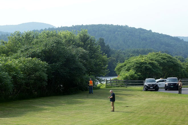 Investigators, including those from the Federal Aviation Administration, gather along the Connecticut River and Route 25 in Bradford, Vt., on July 16, 2021, following the death of a hot-air balloonist Brian Boland.