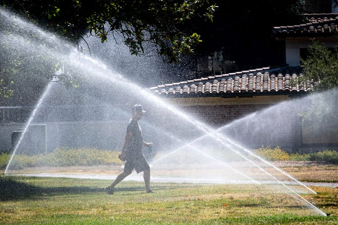 A walker at North Hollywood park gets refreshed along the walking path from the park sprinklers Monday, June 28, 2021. Temperatures around Southern California are expected to be in the triple digits again this week.