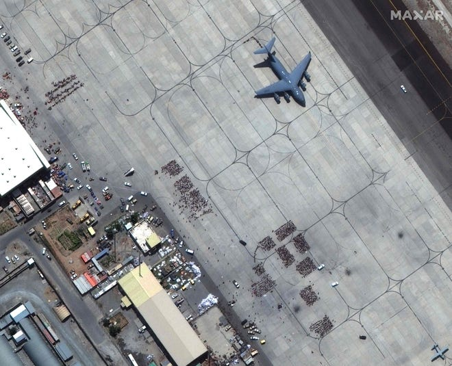 This handout satellite image released by Maxar Technologies shows crowds of people waiting on the tarmac at Kabul's Hamid Karzai International Airport in Afghanistan, with a C-17 transport aircraft ready, on Aug. 23, 2021.