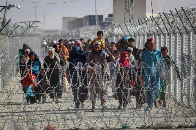 Afghans walk along fences as they arrive in Pakistan through the Pakistan-Afghanistan border crossing point in Chaman on Aug. 24, 2021, following Taliban's military takeover of Afghanistan.