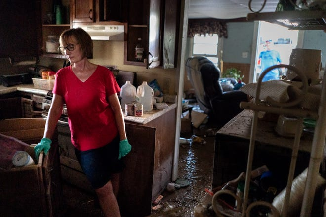 Jaquita Buchanan works on salvaging items from her mother's home in Waverly, Tenn., Monday, Aug. 23, 2021. Her mother escaped from the home safely, but her step-father died while assisting a neighbor. As much as 17 inches of rain hit Humphreys County Saturday, causing flood waters to surge throughout the area killing dozens of people.