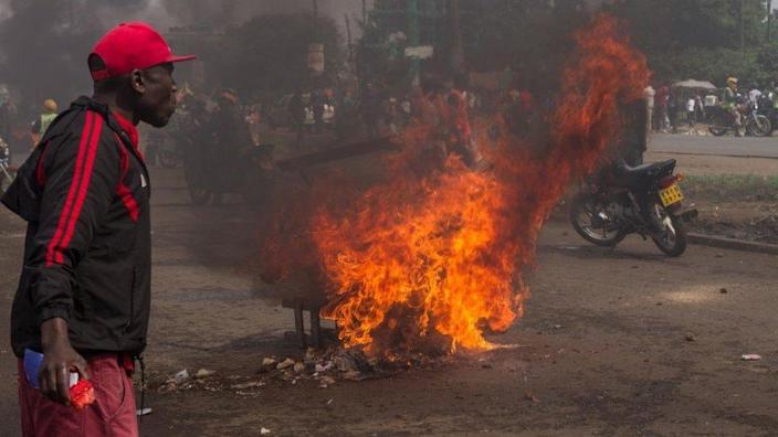 Burning road barricade seen during the protest as people walk near by. The welcome rally for returning opposition candidate Raila Odinga back to Kenya turned into a riot, with burning road barricades, stone throwing, tear gas grenades and water cannons (2017/11/17)