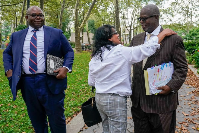 R. Kelly supporter Carlotte Woods, center, of Kentucky, hugs his attorney Deveraux Cannick, right, as he returns to court after a lunch break in the R&B star's trial on Aug. 19, 2021, in New York.