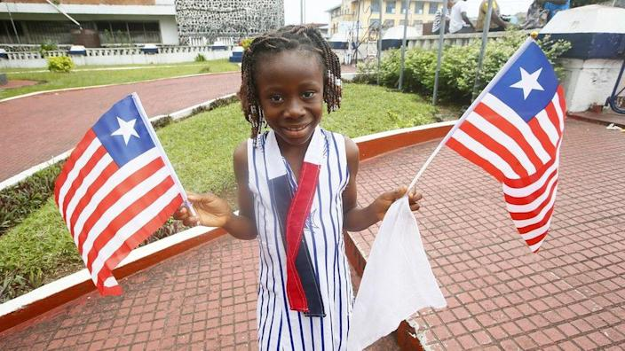 A girl poses with Liberian national flag on the National flag day in Monrovia, Liberia, 24 August 2021