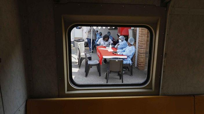 Healthcare workers wait to register people for vaccines outside a Transvaco train