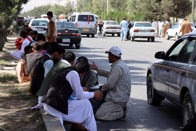 Hundreds of people, some holding documents, gather near an evacuation control checkpoint on the perimeter of the Hamid Karzai International Airport, in Kabul, Afghanistan, on Aug. 27, 2021.