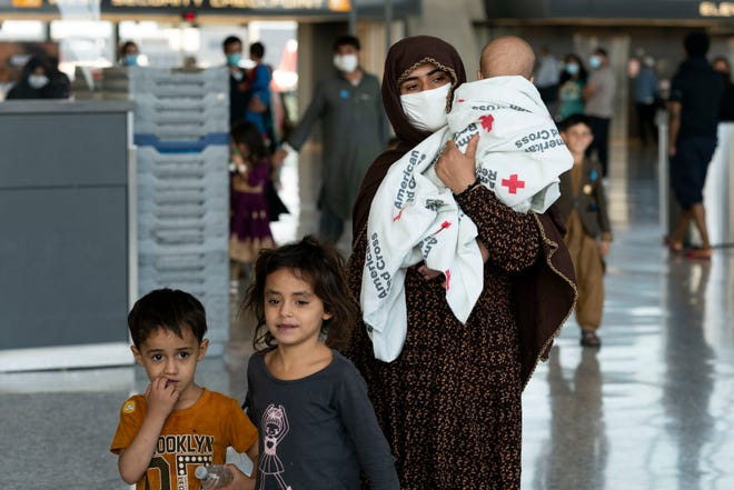 Families evacuated from Kabul, Afghanistan, walk through the terminal before boarding a bus after they arrived at Washington Dulles International Airport, in Chantilly, Virginia, on Aug. 27, 2021.