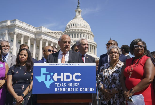 Rep. Chris Turner, chairman of the Texas House Democratic Caucus, center, is joined by Democratic members of the Texas legislature at a news conference at the Capitol in Washington, Tuesday, July 13, 2021, after they left Austin hope to deprive the Legislature of a quorum — the minimum number of representatives who have to be present for the body to operate. They are trying to kill a Republican bill making it harder to vote in the Lone Star State.