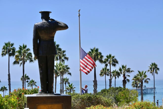 Wayne Eggleston lowers a U.S. flag to half-staff on Friday at Park Semper Fi in San Clemente, California.