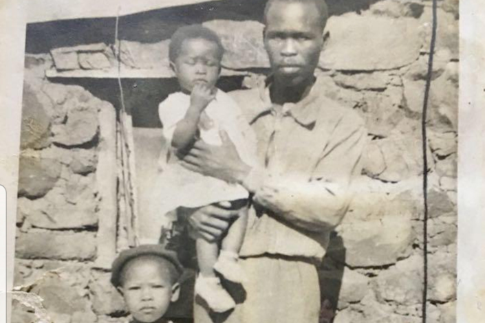 A photo of Agnes Sithole with her younger sister and father outside the house she was born in
