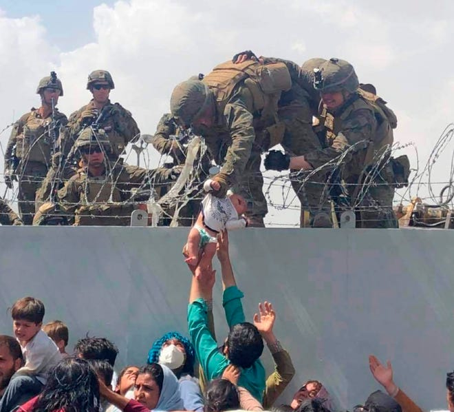 In this image from video provided by Omar Haidari and taken on Thursday, Aug. 19, 2021, which shows a baby being lifted across a wall at Kabul Airport in Afghanistan by US soldiers. The image grabbed from footage, taken on Thursday, showed the infant being pushed up to the soldiers by people in the crowd gathered outside the airport, amid the chaos of those fleeing the Taliban takeover of the country.
