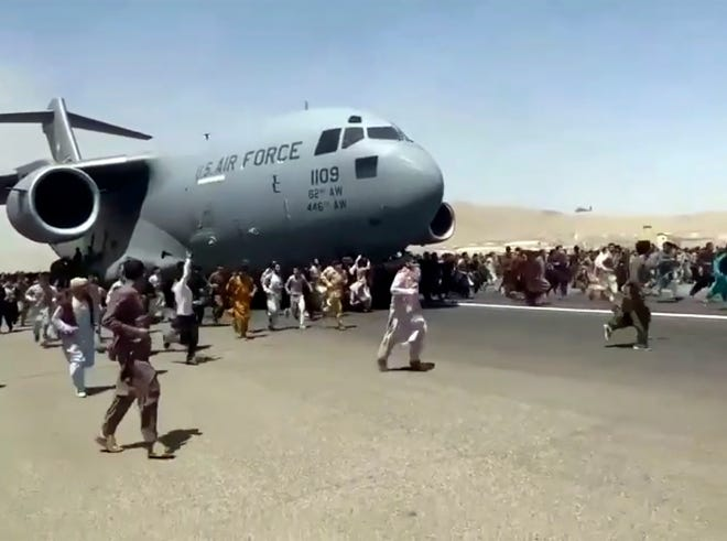 FILE - In this Apug. 16, 2021 file photo, hundreds of people run alongside a U.S. Air Force C-17 transport plane as it moves down a runway of the international airport, in Kabul, Afghanistan.  Twin tragedies on opposite sides of the world are piling misery on people that have seen far more than their share. In Afghanistan, a group of gunmen known for sadistic tyranny rocketed back into power after 20 years as Western and Afghan leaders walked away with a sad shrug.(Verified UGC via AP, File)