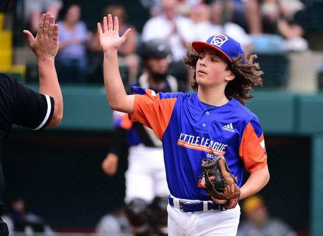 Michigan starting pitcher Ethan Van Belle high fives his coach after retiring the side in the second inning of the Little League World Series championship game.