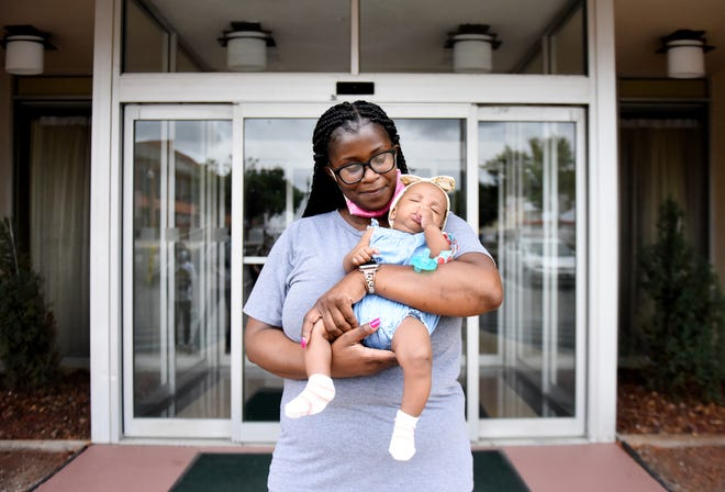 Nikeia Washington from Vacherie, Louisiana holds her granddaughter, Halia Zenon, at a hotel in downtown Shreveport where they have evacuated because of hurricane Ida.