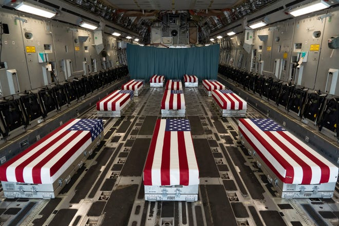 In this image provided by the U.S. Air Force, flag-draped transfer cases line the inside of a transport plane on Sunday prior to a dignified transfer at Dover Air Force Base in Delaware. The fallen service members were killed while supporting non-combat operations in Kabul, Afghanistan.