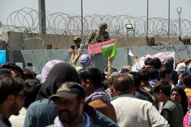 A U.S. soldier holds a sign indicating a gate is closed as hundreds of people gather some holding documents, near an evacuation control checkpoint on the perimeter of the Hamid Karzai International Airport, in Kabul, Afghanistan, Thursday, Aug. 26, 2021. Western nations warned Thursday of a possible attack on Kabul's airport, where thousands have flocked as they try to flee Taliban-controlled Afghanistan in the waning days of a massive airlift.