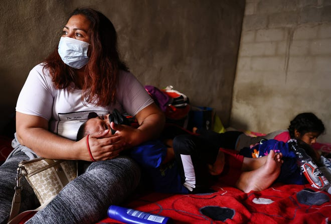 A mother holds her child as asylum-seeking migrants rest in a migrant shelter on July 21, 2021 in Tijuana, Mexico.
