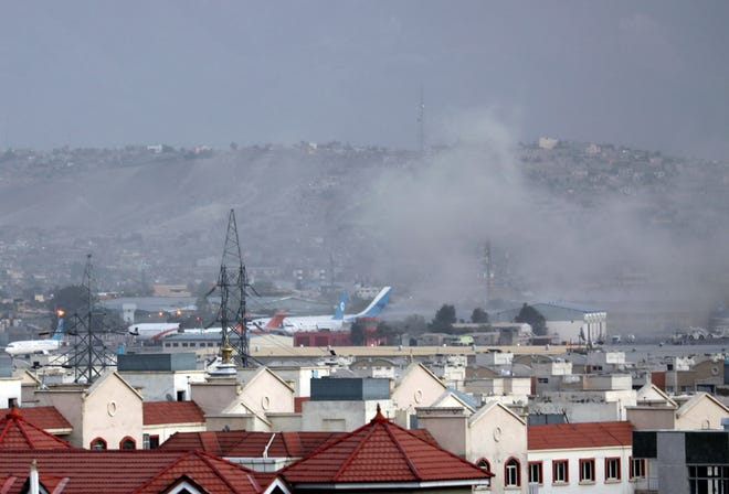 Smoke rises from explosion outside the airport in Kabul, Afghanistan, Thursday, Aug. 26, 2021. The explosion went off outside Kabul's airport, where thousands of people have flocked as they try to flee the Taliban takeover of Afghanistan. Officials offered no casualty count, but a witness said several people appeared to have been killed or wounded Thursday. (AP Photo/Wali Sabawoon) ORG XMIT: XRG128