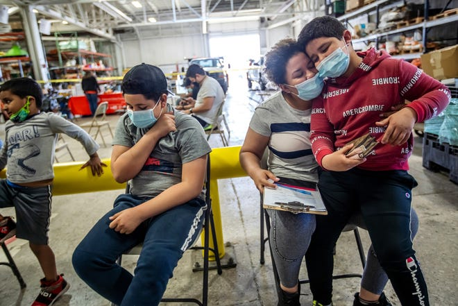 Indira Cisneron holds her son German Vazquez while waiting to get her first COVID-19 vaccine shot as her other son Gabriel Vasquez, left, 13,  waits in southwest Detroit.