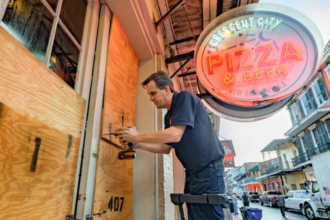 Michael Richard boards up Crescent City Pizza on Bourbon Street in New Orleans' French Quarter before landfall of Hurricane Ida on Aug. 28, 2021.