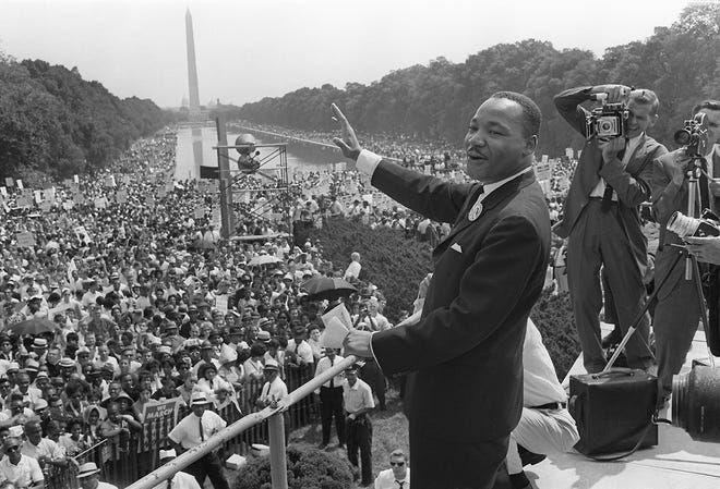 The Rev. Martin Luther King Jr. waves to supporters during the March on Washington at the National Mall in Washington, D.C., on Aug. 28, 1963