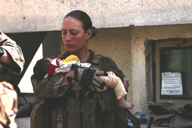 Marine Sgt. Nicole Gee, seen holding a baby at Kabul's airport, was one of the 13 U.S. service members killed in the Aug. 26 bombing in Afghanistan.