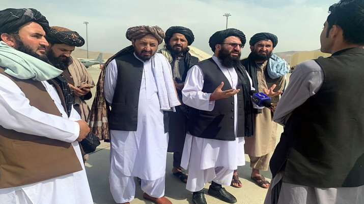 Taliban officials are interviewed by journalists inside the