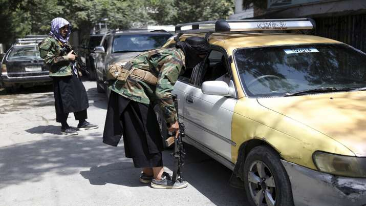 Taliban fighters search a vehicle at a checkpoint on the
