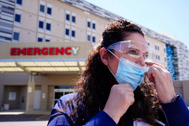 ICU nurse Caroline Maloney, who has been treating COVID-19 patients through the entire pandemic, wears a mask on Thursday outside Scottsdale Osborn Medical Center in Scottsdale, Arizona.