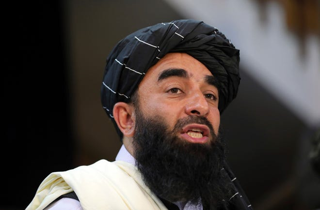 """In this Aug. 17, 2021 file photo, Taliban spokesman Zabihullah Mujahid speaks at at his first news conference, in Kabul, Afghanistan. Mujahid said Tuesday at a press conference in Kabul that the U.S. must complete its evacuation of people from Afghanistan by the Aug. 31 date the Biden administration set for the withdrawal of all American troops. Mujahid said his group will accept """"no extensions"""" to the deadline."""