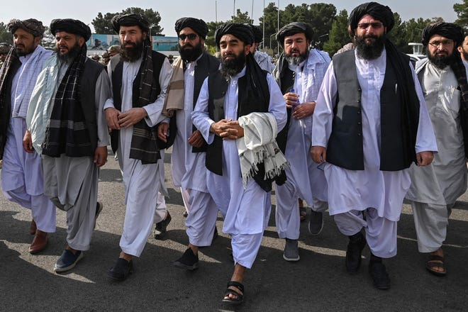 Taliban spokesman Zabihullah Mujahid, at center holding shawl, arrives accompanied by officials to address a media conference at the airport in Kabul on Aug. 31, 2021. The Taliban joyously fired guns into the air and offered words of reconciliation as they celebrated defeating the United States and returning to power after two decades of war that devastated Afghanistan.