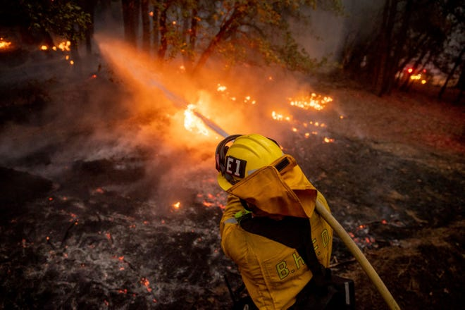 A firefighter hoses down flames from the Dixie Fire in Genesee, Calif., on Saturday, Aug. 21, 2021.