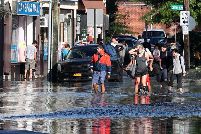 A family wades in the water as they evacuate along  Mamaroneck Avenue in Mamaroneck, N.Y., Sept. 2, 2021. Rains from Ida flooded the area overnight.