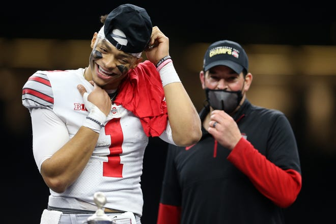 Justin Fields celebrates with Ohio State coach Ryan Day after defeating the Clemson Tigers in the Sugar Bowl to earn a spot in the national title game.