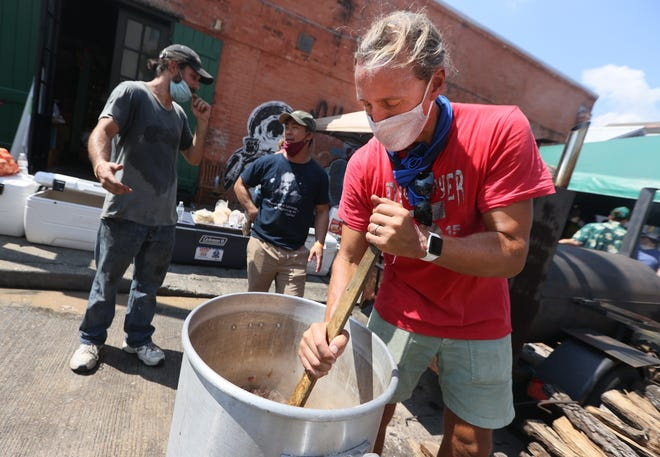 Ryan Prewitt, the James Beard Awarded chef of Peche, mixes a cabbage stew outside of Howlin Wolf where he joins other volunteers using donated foods from local restaurants and patrons to help cook and feed more than 5000 meals on Saturday, Sept. 4, 2021.