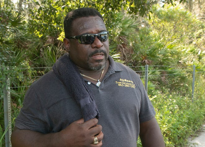 Jeremiah Benson talks on Monday morning about the shooting and the four killings that occurred at a home next to property he is working on along North Socrum Loop Road in North Lakeland on Sunday.