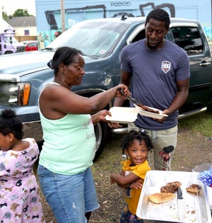 """Paula Calice serves food to a friend in New Orleans on Sept. 6. Calice and her husband cook donated food for area residents waiting for power to be restored after Hurricane Ida. Smiling at the camera is Zaryah """"RaRa"""" Manning, 3."""