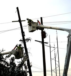 Utility workers repair broken power poles and lines as they work to restore power to New Orleans on Monday, Sept. 6, 2021, following the passage of Hurricane Ida.