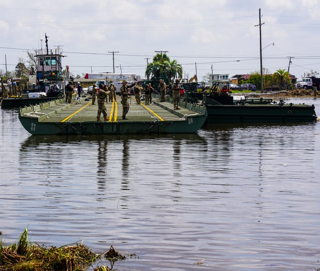 Members of the National Guard construct a temporary floating bridge to reach the island of Barataria, Louisiana, which was cut off from the mainland after the passage of Hurricane Ida.