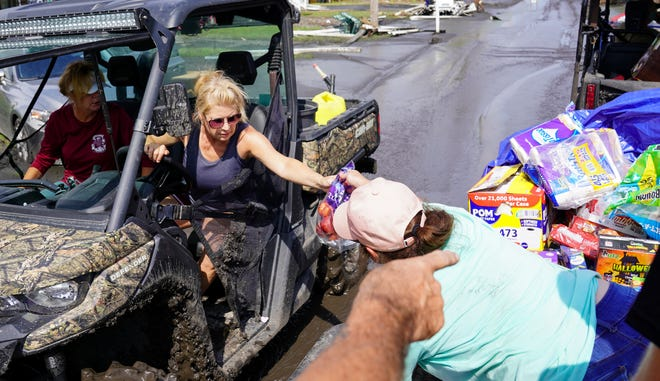 Tess Coulon hands supplies to a resident of the island of Barataria, Louisiana. Barataria was cut off from the mainland after the passage of Hurricane Ida and volunteers have been delivering food and other supplies to stranded residents.