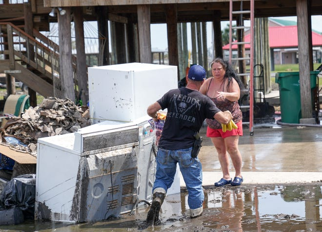Wading through deep mud, Romeo Mamolo III hands fresh fruit to a woman stuck at her home on the island of Barataria, Louisiana. Barataria was cut off from the mainland after the passage of Hurricane Ida and volunteers have been delivering food and other supplies to stranded residents.
